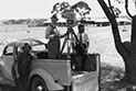 Cinematographer Bert Ive standing in the back of a utility truck behind a camera on a tripod. He is at the side of an unsealed road in the outback with two other men.