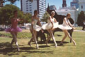 A group of ballet dancers in pink and white tutus, dancing in a park in central Adelaide.  They are with a pianist and a grand piano.