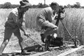 Director John Heyer pulling cameraman Reg Pearse on a tracking device whilst filming a scene in a wheat field.