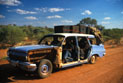 The Bush Mechanics cast inside an EJ Holden station wagon with doors removed in the outback.