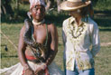 Producer/presenter Caroline Jones beside an indigenous Guarani man in ceremonial dress, with a python on his shoulder.