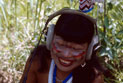 Indigenous Guarani woman in ceremonial dress, listens to sound recordings with headphones.