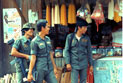 Military soldiers stand on the street beside a shop.