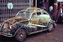 Volkswagon with decorative body made from wrought iron parked outside a store.