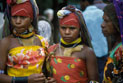 Three Papua New Guinean women wearing colourful headgear.