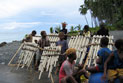 Local villagers on beach constructing walls for traditional housing, Weather Coast.